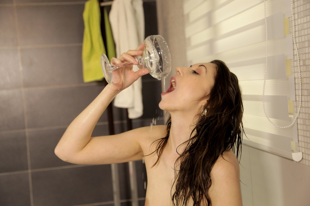 Stunning brunette drinks her pee from a glass